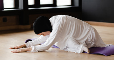 Young Muslim lady stretching in contemporary studio